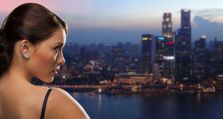 PRETTY WOMEN: people, holidays, jewelry and luxury concept - woman face with diamond earring over night singapore city background