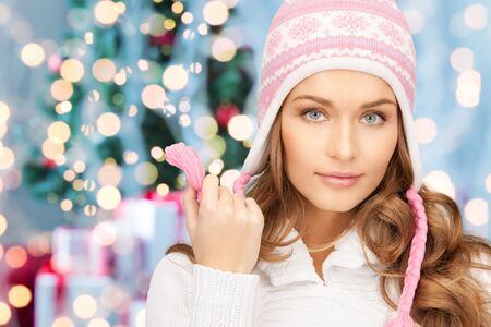 christmas hat: winter holidays and people concept - happy young woman in winter hat with over christmas tree lights background Stock Photo
