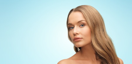 women smiling: beauty, people, hair care and health concept - beautiful young woman face over blue background