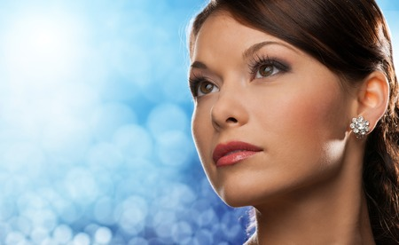 blue face: people, holidays, jewelry and luxury concept - woman face with diamond earring over blue lights background
