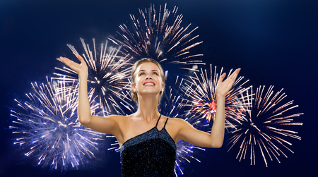 arms up: people, happiness, holidays and glamour concept - smiling woman raising hands and looking up over firework on dark blue background