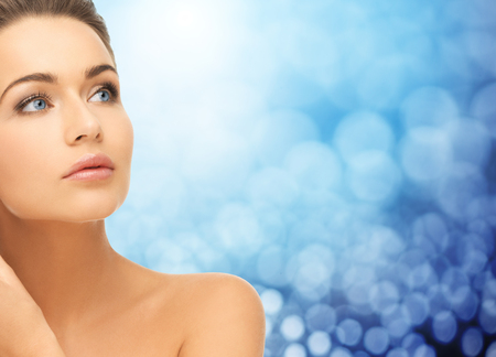 blue face: beauty, people and health concept - beautiful young woman face and bare shoulder over blue lights background Stock Photo
