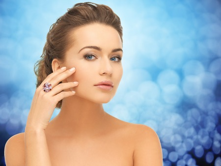 glamour luxury: people, jewelry, luxury and glamour concept - woman wearing diamond ring over blue lights background