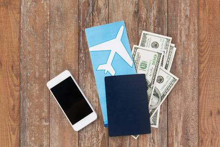 tourism, travel and objects concept - air ticket, money, smartphone and passport on wooden table background