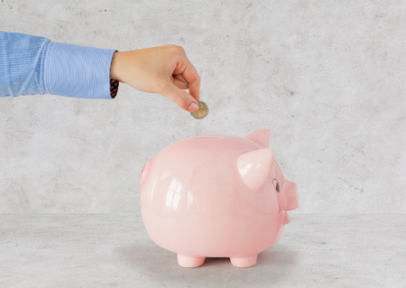 coin bank: business, finance, investment, money saving and budget concept - close up of hand putting coin into piggy bank over gray  concrete background Stock Photo