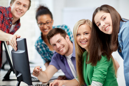 education, people, friendship, technology and learning concept - group of happy international high school students or classmates in computer class