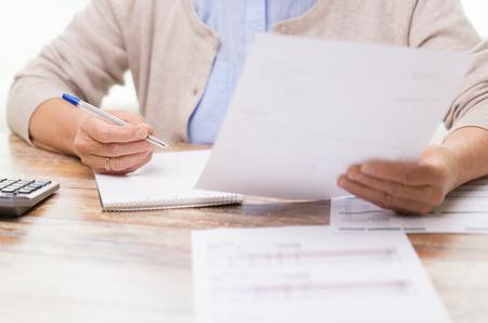 calculadora: negocio, ahorros, seguros de renta vitalicia, la edad y las personas concepto - mujer mayor con papeles o proyectos de ley y la escritura calculadora en casa Foto de archivo