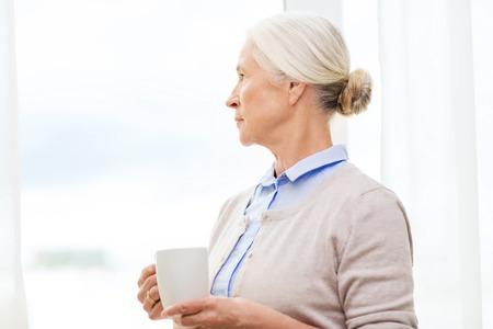 femme triste: l'âge, la solitude et les gens concept - femme âgée solitaire avec tasse de thé ou de café regardant par la fenêtre à la maison