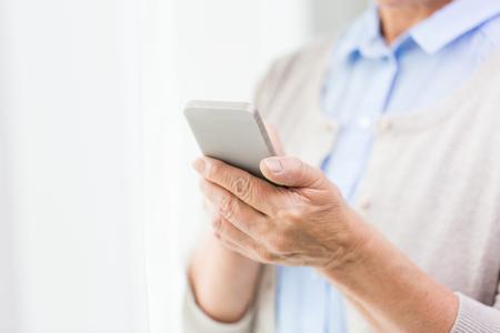 llamando: la tecnología, la era de la comunicación y el concepto de la gente - cerca de la mujer mayor manos con el mensaje de los mensajes de texto de teléfonos inteligentes en el hogar
