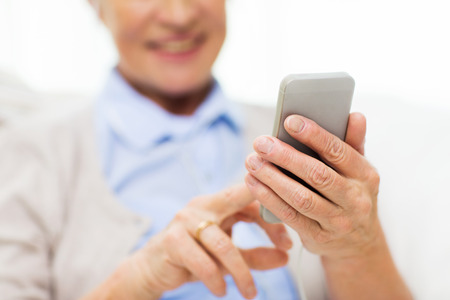 dialing: technology, communication age and people concept - close up of happy senior woman with smartphone texting message at home Stock Photo