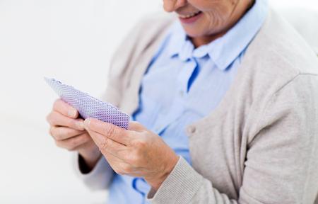 mujer alegre: edad, juego, juego de azar, el póquer y la gente concepto - cerca de la sonrisa feliz de la mujer mayor jugando a las cartas en casa