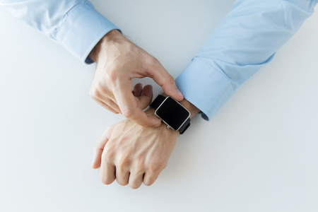 business, technology and people concept - close up of male hands setting smart watch at home Stock Photo