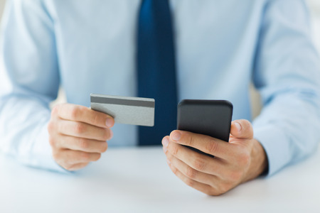 cash: business, technology, cash free and internet people concept - close up of male hands holding smart phone and credit card at office Stock Photo