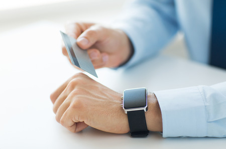 emoney: business, technology, cash free and internet people concept - close up of male hands with smart watch and credit card at office Stock Photo