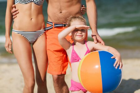 small girl: family, childhood, travel and people concept - close up of happy man, woman and little girl in sunglasses with inflatable ball on summer beach