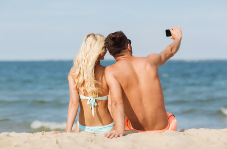 fling: love, travel, tourism, technology and people concept - smiling couple on vacation in swimwear sitting on summer beach and taking selfie with smartphone from back