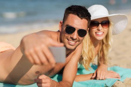 사랑, 여행, 관광, 기술 및 사람들이 개념 - 수영복 및 선글라스에 휴가에 웃는 커플 여름 해변에서 스마트 폰과 함께 selfie을 복용 스톡 콘텐츠