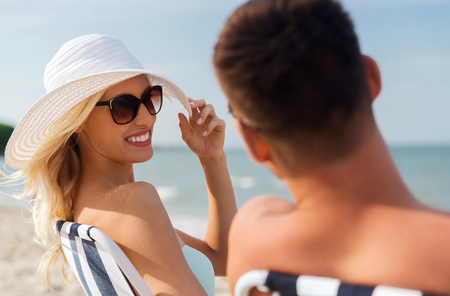 fling: love, travel, tourism, summer and people concept - smiling couple on vacation sunbathing on beach