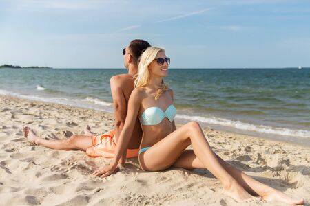 fling: love, travel, tourism, summer and people concept - smiling couple on vacation in swimwear sitting on beach back to back Stock Photo