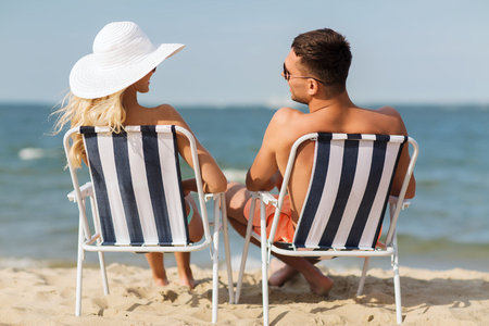 fling: love, travel, tourism, summer and people concept - smiling couple on vacation in swimwear sitting in chairs and sunbathing on beach from back