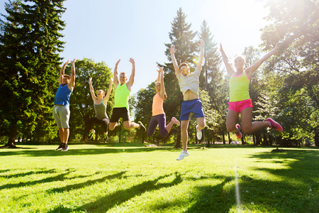 fitness, sport, friendship and healthy lifestyle concept - group of happy teenage friends jumping high outdoors Stockfoto