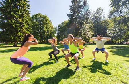 warm up exercise: fitness, sport, friendship and healthy lifestyle concept - group of happy teenage friends exercising and doing squats at boot camp