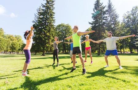 exteriores: fitness, deporte, la amistad y el concepto de estilo de vida saludable - grupo de amigos adolescentes feliz ejercicio en el campo de entrenamiento