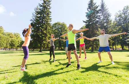 fitness instructor: fitness, sport, friendship and healthy lifestyle concept - group of happy teenage friends exercising at boot camp