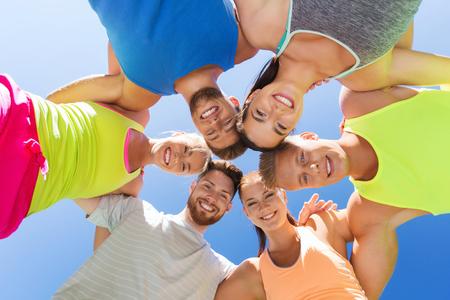 circulo de personas: fitness, deporte, la amistad y el concepto de estilo de vida saludable - grupo de amigos adolescentes felices en c�rculo al aire libre