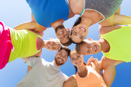 friendship circle: fitness, sport, friendship and healthy lifestyle concept - group of happy teenage friends in circle outdoors Stock Photo