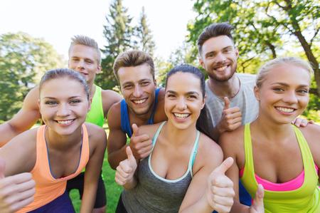피트 니스, 스포츠, 우정과 건강 한 라이프 스타일 개념 - 야외에서 엄지 손가락을 보여주는 행복 한 십 대 친구의 그룹 스톡 콘텐츠