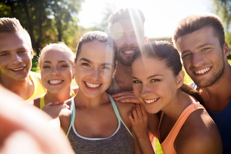 pareja adolescente: fitness, deporte, la amistad, la tecnolog�a y el concepto de estilo de vida saludable - grupo de amigos adolescentes felices que toman selfie con el tel�fono inteligente al aire libre Foto de archivo