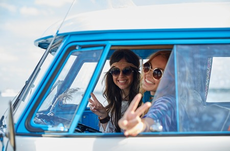 van: summer holidays, road trip, vacation, travel and people concept - smiling young hippie women driving minivan car and showing peace gesture
