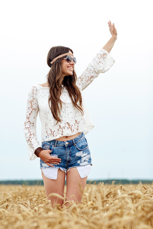 gipsy: nature, summer, youth culture, gesture and people concept - smiling young hippie woman in sunglasses on cereal field waving hand
