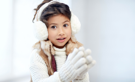 preteen asian: winter, people, happiness concept - happy little girl wearing earmuffs