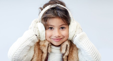 winter, people, happiness concept - happy little girl wearing earmuffs