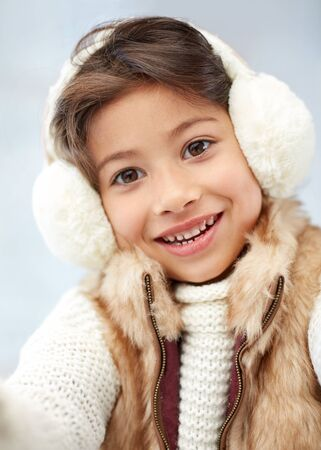 small girl: winter, people, happiness concept - happy little girl wearing earmuffs