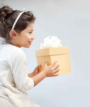 receiving: holidays, presents, christmas, childhood and people concept - smiling little girl with gift box at home