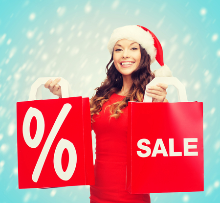 christmas woman: shopping, sale, gifts, christmas, x-mas concept - smiling woman in red dress and santa helper hat with shopping bags Stock Photo