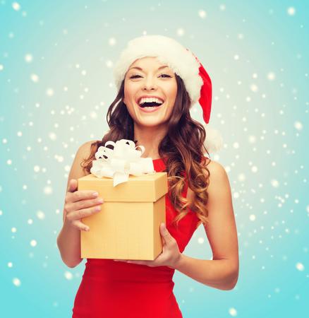 Navidad, Navidad, año nuevo, invierno, concepto de la felicidad - mujer sonriente en el sombrero del ayudante de santa con caja de regalo