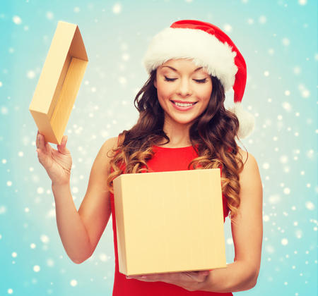 fancy box: christmas, x-mas, winter, happiness concept - smiling woman in santa helper hat with gift box