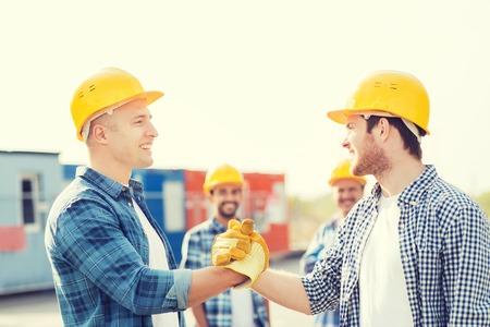 Bedrijf, gebouw, teamwork, gebaar en mensen concept - groep lachende bouwers in hardhats elkaar met handdruk in openlucht Stockfoto