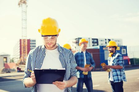 taking notes: business, building, teamwork and people concept - group of builders in hardhats with clipboard outdoors