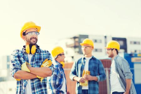 비즈니스, 건물, 팀웍 및 사람들이 개념 - 클립 보드 야외 hardhats에서 웃는 빌더의 그룹