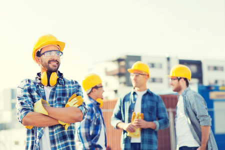 happy workers: business, building, teamwork and people concept - group of smiling builders in hardhats with clipboard outdoors Stock Photo
