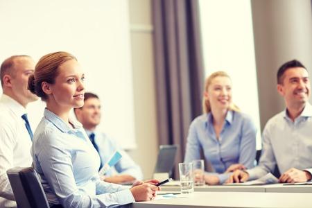 ビジネス、人々 とチームワークの概念 - ビジネスマンのオフィスでのプレゼンテーション会議を笑顔のグループ