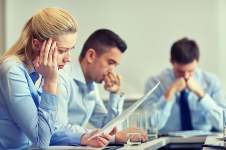 developers: business, teamwork, people and crisis concept - business team sitting sad and solving problem in office