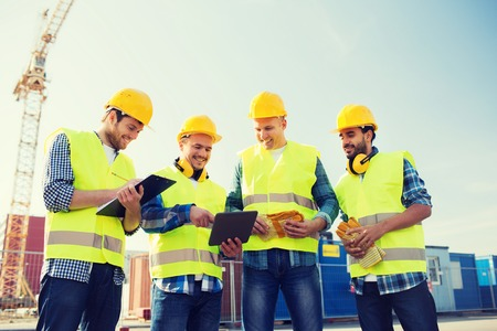 happy workers: business, building, teamwork, technology and people concept - group of smiling builders in hardhats with tablet pc computer and clipboard outdoors
