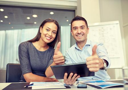 het bedrijfsleven, mensen, technologie en teamwork concept - glimlachende zakenman en zakenvrouw met tablet pc computer zien thumbs up gebaar bijeenkomst in het kantoor