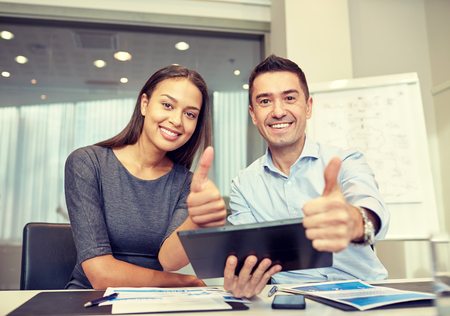 business, people, technology and teamwork concept - smiling businessman and businesswoman with tablet pc computer showing thumbs up gesture meeting in office Foto de archivo